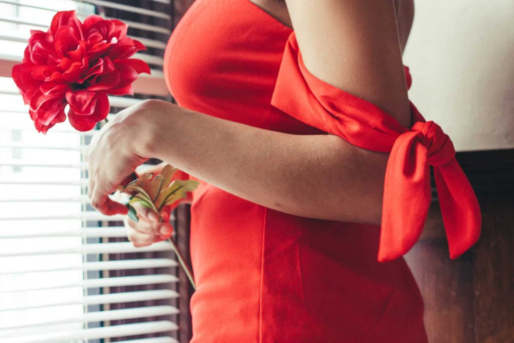 Close up of sleeve tie details on red dress, perfect for a night out with your significant other.