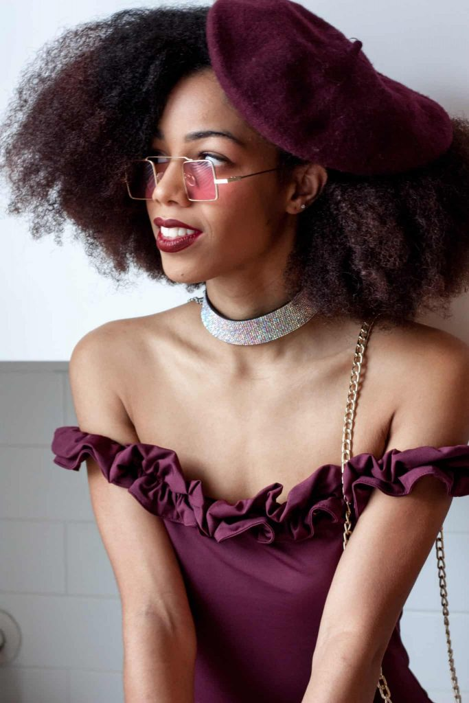 Black woman with Natural Hair Afro weating a purple Beret with Sparkly choker
