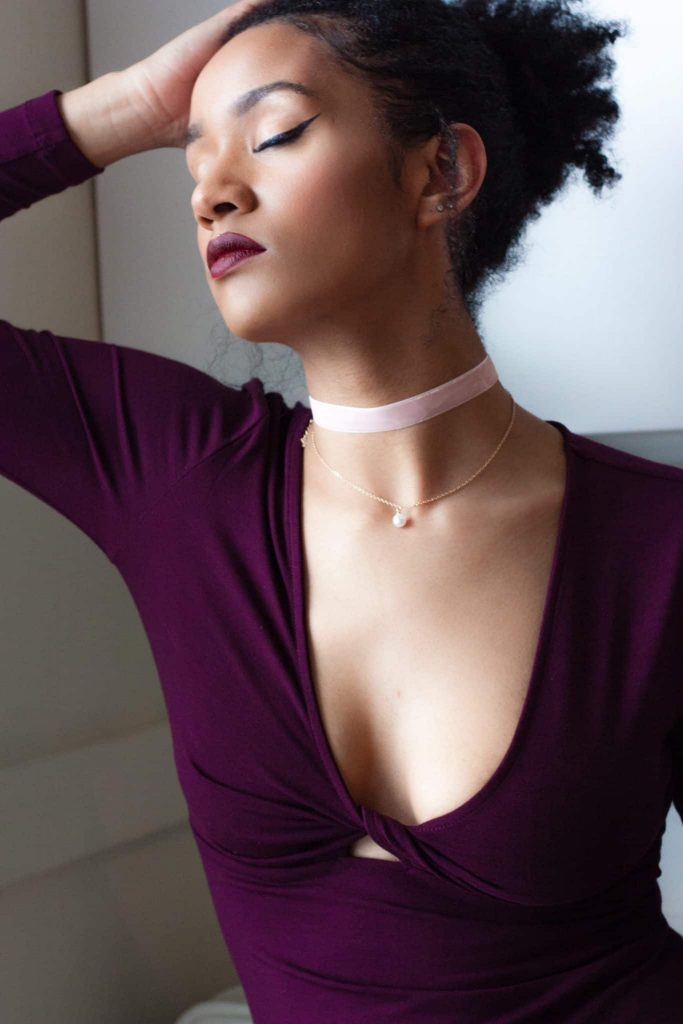 Black woman in contemplation | Low-cut simple dress for a night out, with pink choker (valentine's day look?)