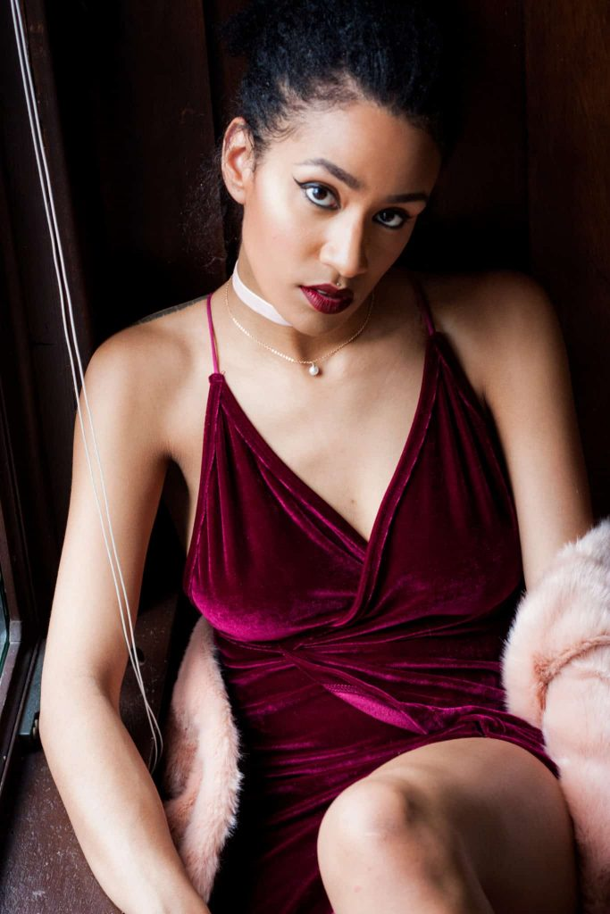 Black woman modelling wine V cut velvet dress. with choker.  for a luxury valentine's day look