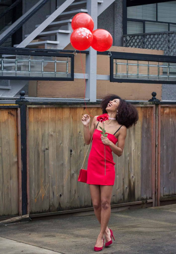Valentine's day date night outfit inspiration. Red Dress, shoes, purse, balloons and flower, on a black model with Natural Hair.