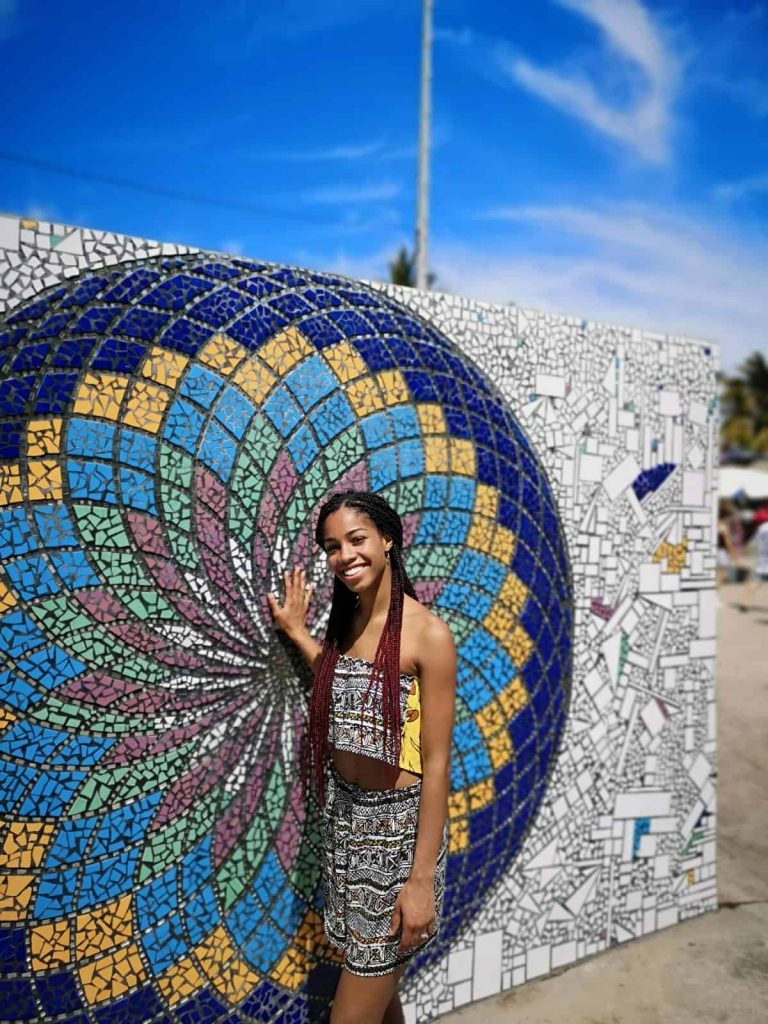 Black Blogger with Burgundy Ombre Colored box braids on Vacation with Mosaic Wall