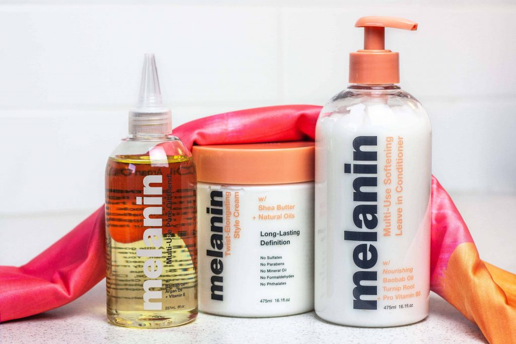 The Golden Trio from Melanin Haircare. Natural Hair careproducts to style the LOC or LCO method. Multi-Use Softening Leave in conditioner, Multi use pure oil blend, twist-elongating style cream. Pictured with satin stretch head wrap in sunset.