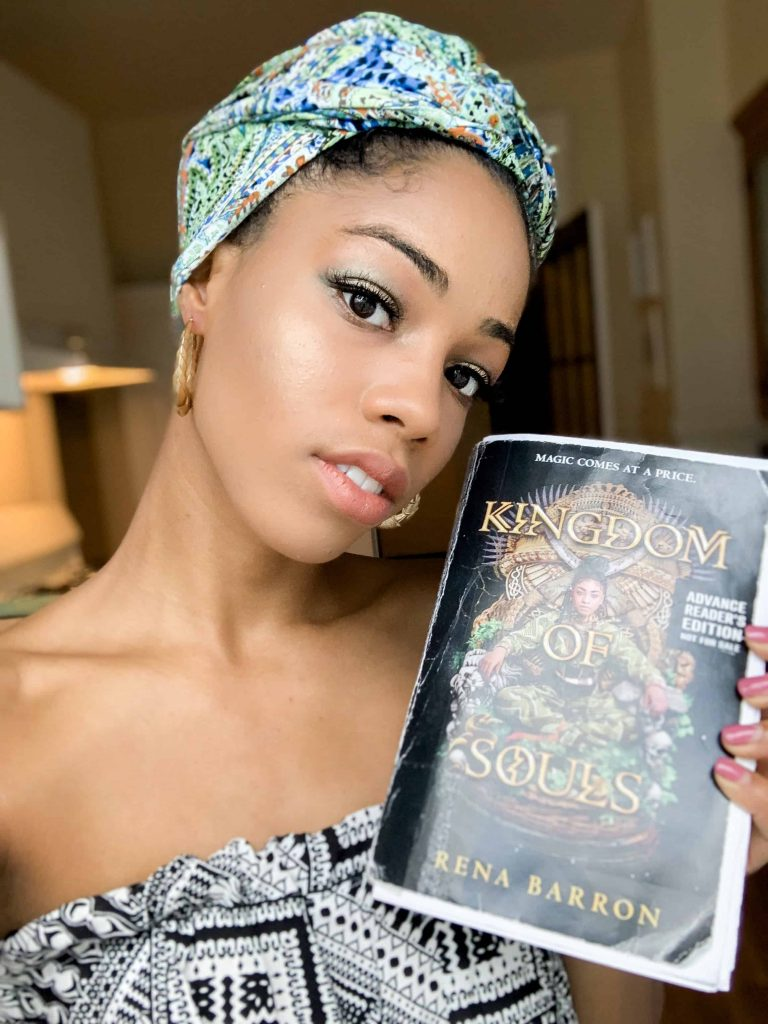 Black Woman Posing with green Head Wrap Style and a Book.