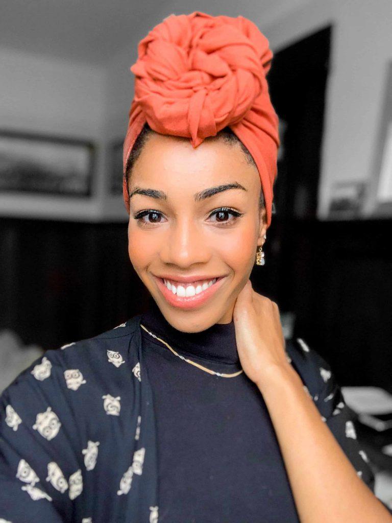 Black woman wearing orange headwrap styles. Tied in a top knot.