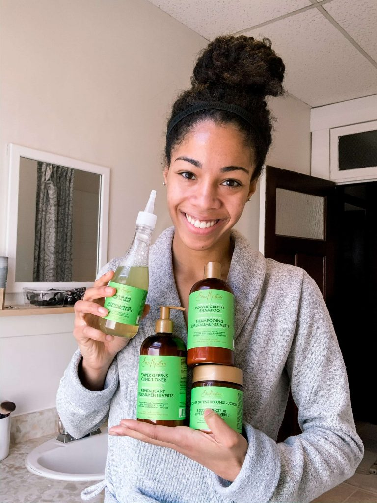 Natural Hair Blogger (Comfygirlcurls) Holding and Reviewing the SheaMoisture Power Greens Collection. Shampoo, Green Tea Hair Rinse, Conditioner, and Reconstructor