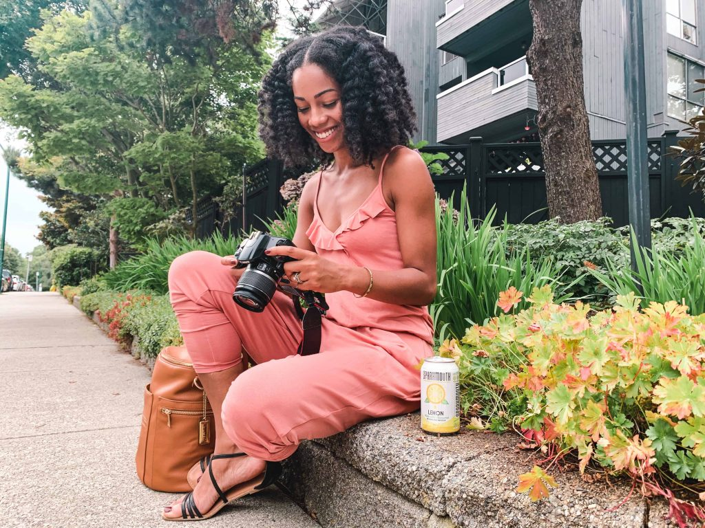 Black Canadian Blogger, Comfy Girl with Curls reviewing photos on camera.  SPARKMOUTH Sparkling Water in lemon. #FindYourSpark