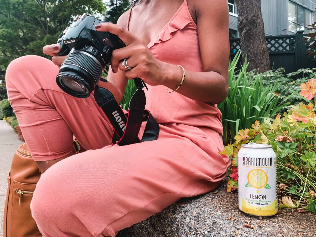 Black Canadian Blogger, Comfy Girl with Curls reviewing photos on camera.  SPARKMOUTH Sparkling Water in lemon. (Close Up). Find Your Spark.