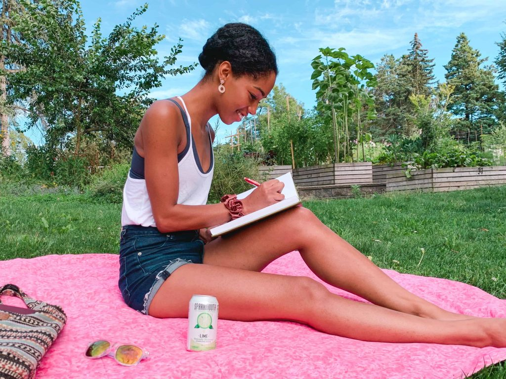 Black Canadian Blogger, Comfy Girl with Curls writing in the park with her SPARKMOUTH Sparkling Water in Lime. Find My Spark.