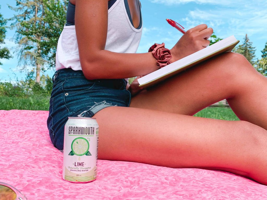 Black Canadian Blogger, Comfy Girl with Curls writing in the park with her SPARKMOUTH Sparkling Water in Lime. (Close up of can)