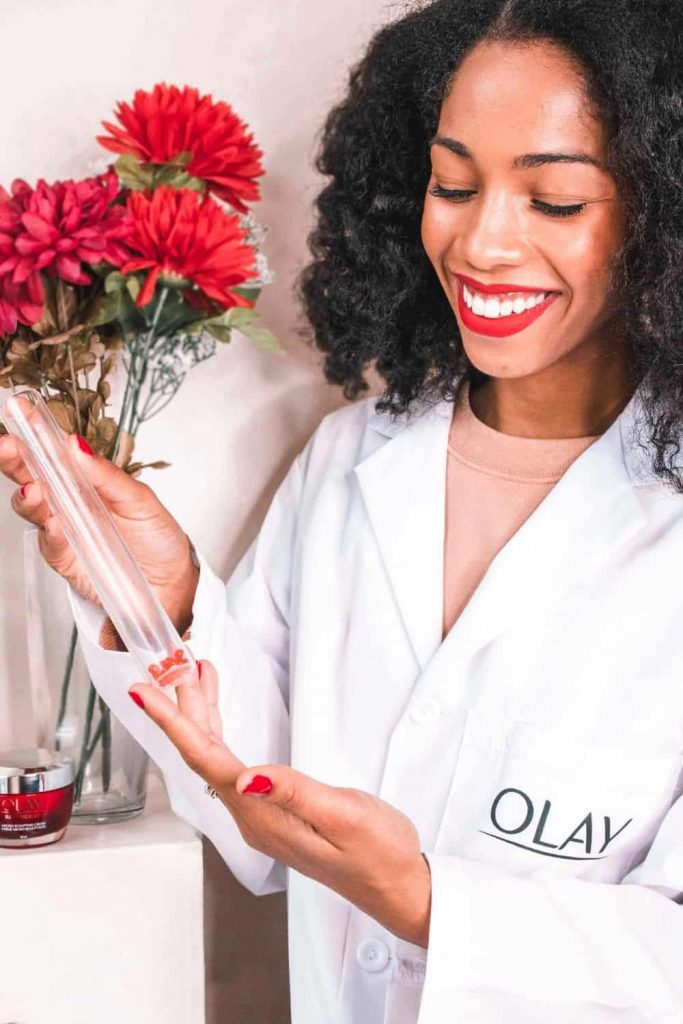 Black Blogger Holding Test Tube for Olay Regenerist Multi-Sculpting Cream Review