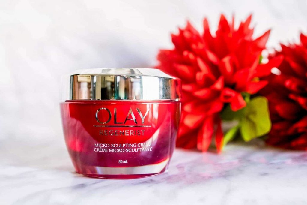 Olay Regenerist Micro-sculpting cream face moisturizer review. Red jar against marble backdrop with red flowers.