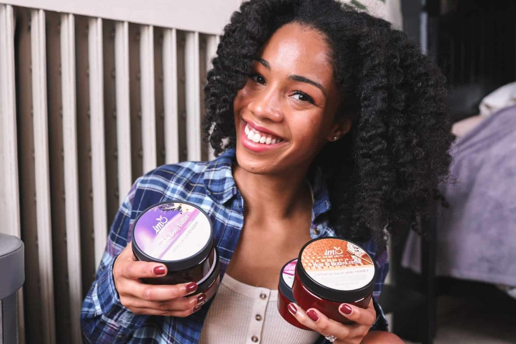 ComfyGirlCurls, Black Blogger holding up hair and body products from Canadian Black-Owned Business
