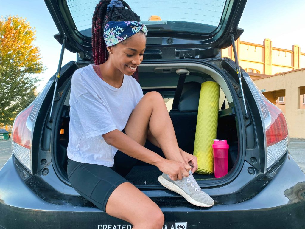 """Black Canadian Blogger sitting in the trunk of an Evo Car Share vehicle, tying her shoe. Answering the question """"Do You Need to own a car in Vancouver"""""""
