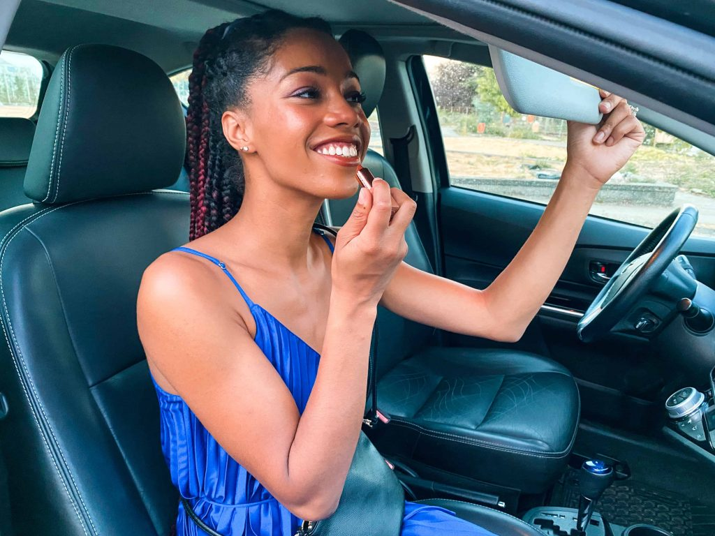 Black Blogger wearing Royal Blue Dress, applying lipstick while sitting in the passenger seat of an Evo Car Share in Vancouver
