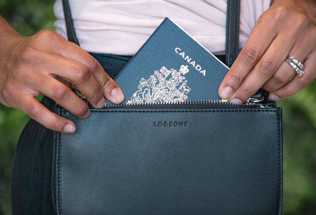 Best convertible bag for Travel: Lo & Sons Waverley 2 in black pictured with a Canadian passport.